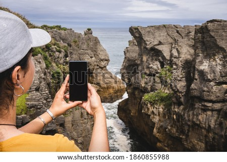Woman taking picture with mobile at Pancake Rocks, famous travel destination in the South Island of New Zealand.