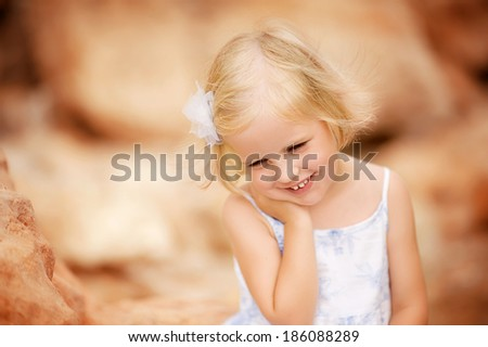 Cute little girl standing in a white dress on the beach. Portrait, eyes closed, a flirt. #186088289