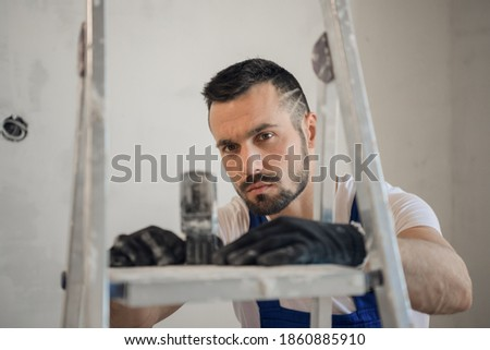 Bearded builder in uniform uses an electronic ruler to work