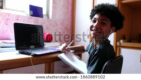 Boy doing homework at home browsing laptop and writing notes. looks at camera smiling Royalty-Free Stock Photo #1860889102