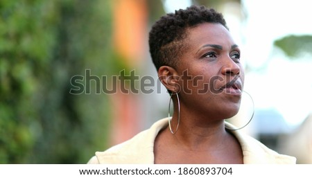 Anxious African woman walking outside. Black person ruminating thoughts Royalty-Free Stock Photo #1860893704