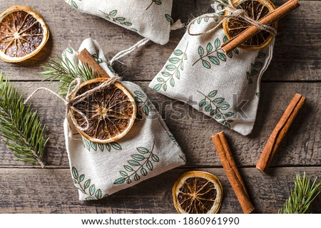 Christmas still life with eco friendly textile gift packaging. Fabric gift pouches decorated by fir tree, dry citrus and cinnamon stick's. Royalty-Free Stock Photo #1860961990