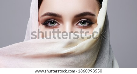 beautiful young woman covered her face in hijab. fashion oriental style woman Royalty-Free Stock Photo #1860993550