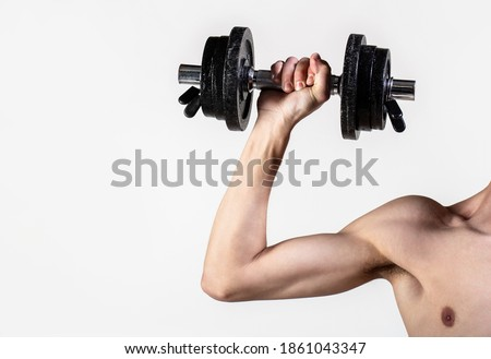 Man hand holding dumbbell in hand. Skinny guy hold dumbbells up in hands. A thin man in sports with dumbbells. Weak hand man lift a weight, dumbbells. Nerd maleraising a dumbbell. Royalty-Free Stock Photo #1861043347