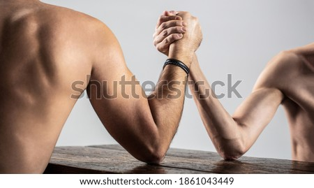 Two man's hands clasped arm wrestling, strong and weak, unequal match. Arm wrestling. Heavily muscled man arm wrestling a puny weak man. Arms wrestling thin hand and a big strong arm in studio.