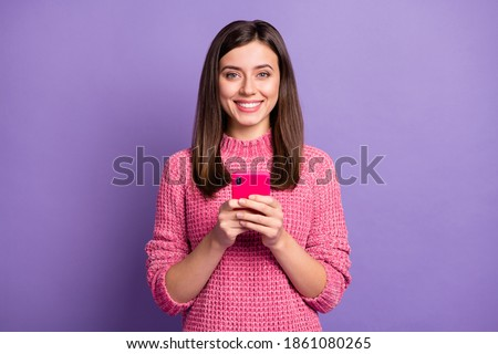 Photo portrait of cheerful nice girl typing comment in inernet isolated on vivid violet color background Royalty-Free Stock Photo #1861080265