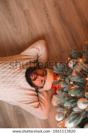 calm adult man under Christmas tree rest after over working season December winter holidays time vertical wallpaper poster concept picture