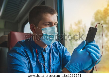 A young european guy in a protective mask and medical gloves is holding a phone and listening to music on headphones #1861219921