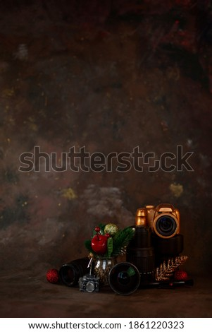 christmas and new year background for photographer. christmas set gold camera and lenses and christmas tree toys on dark background with soft selective focus. vertical orientation