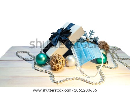 Christmas composition with a gift box, snowflake, disposable mask and Christmas decorations on a white wooden table. The image is isolated on a white background.