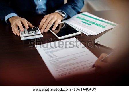 Close-up of financial consultant using calculator while his client is signing paperwork during the meeting.  Royalty-Free Stock Photo #1861440439