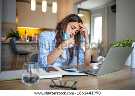 Woman working in the office and having difficulties breathing with face mask, she is pulling the mask down. The woman had to remove the mask to breathe after having to wear it for a long time Royalty-Free Stock Photo #1861441990