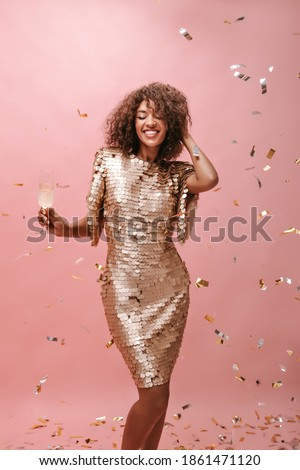 Cheerful girl with curly hairstyle in shiny trendy dress holding glass with drink and smiling with closed eyes on isolated backdrop.. Royalty-Free Stock Photo #1861471120