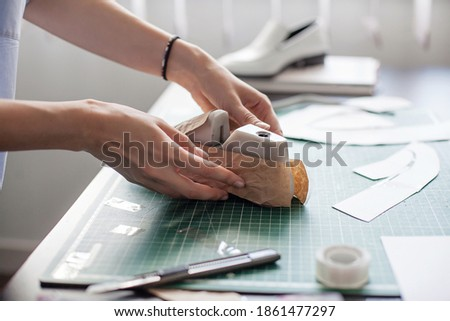 Modelling design of a shoes. Workplace of shoe designer. Hands of designer draw a shoe design on a new shoes at his workshop. Royalty-Free Stock Photo #1861477297