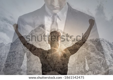 Physically, and mentally strong young businessman man with fist in the air feeling victorious and motivated. double exposure.  Royalty-Free Stock Photo #1861542475
