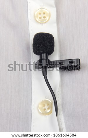 Audio recording of sound on a condenser microphone. The lavalier microphone is secured with a clip on a woman's shirt close-up