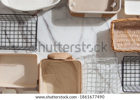 Top view of empty closet organization boxes and steel wire baskets in different shape placed on white marble table with copy space. Marie Kondo's hikidashi boxes for tidying clothes and drawer storage Royalty-Free Stock Photo #1861677490