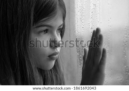 A little, young girl is sitting by the window and is sad, children's problems, loneliness, concept. Black and white photo