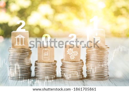 Coins stack and number 2021 on square wood and icon on nature background, Money spending planning, plant growing up on coins and investment budget, Save money for prepare in the future, new year