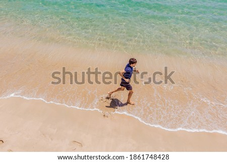 Runner running on beach by the ocean - view from above. Man athlete training cardio jogging doing morning workout. Hero aerial drone view shot, lots of copy space