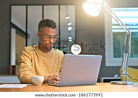 Portrait of african american trendy guy working from home on laptop  Royalty-Free Stock Photo #1861773991