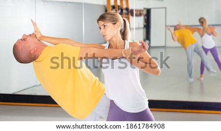 Young woman practicing basic self-defense techniques while training in gym with male partner, performing palm heel strike in chin.. Royalty-Free Stock Photo #1861784908