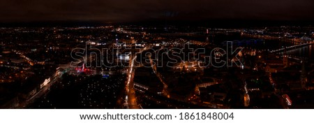 Panoramic view of city Riga center over old town at night. Long exposure night photography made with a drone. River Daugava, Opera house, Monument of Freedom.