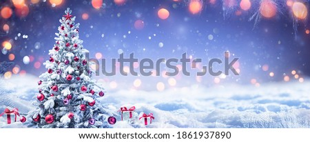 Snowy Christmas Tree With Red Ornament And Present Boxes In A Winter Landscape Royalty-Free Stock Photo #1861937890