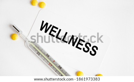 On the business card is the text WELLNESS, next to a thermometer and yellow pills.