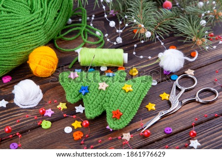 Handmade crocheted Christmas tree from green yarn, New Year's gift and table decoration. Small multi-colored buttons. Dark wooden background. Amigurumi, toy Royalty-Free Stock Photo #1861976629