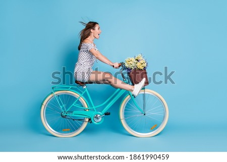 Full length profile photo of crazy girl drive bike raise legs wear dotted short dress footwear isolated blue color background Royalty-Free Stock Photo #1861990459