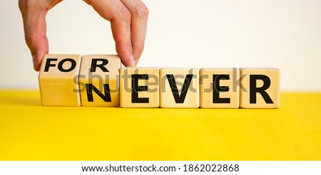 Forever or never. Male hand flips wooden cubes and changes the word 'never' to 'forever'. Beautiful yellow table, white background, copy space. Never or forever concept.