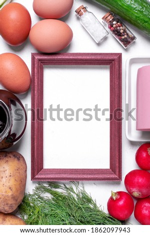 Ingredients to make Okroshka cold soup. Sausage, radish, potato, cucumber, eggs, kvass, herbs and spices around the picture frame on the white table. Top view