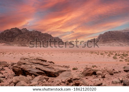 Fantastic view of the endless arid valley, Wadi Rum desert, Jordania. Spectacular sky with large red dramatic clouds, mountain range, lots of red sand and a few bushes and rocks in the background. Royalty-Free Stock Photo #1862120320
