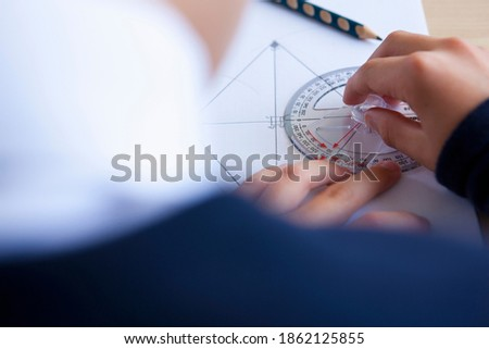 A high angle close up shot of a student's hand using a protractor on a desk.