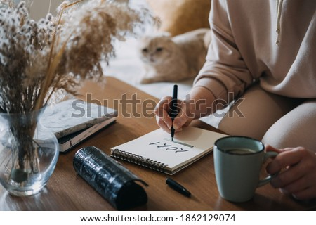 2021 goals, new year resolution, planning. Woman writing in Notebook with text 2021 loading on the table in apartments with cat. Selective focus #1862129074
