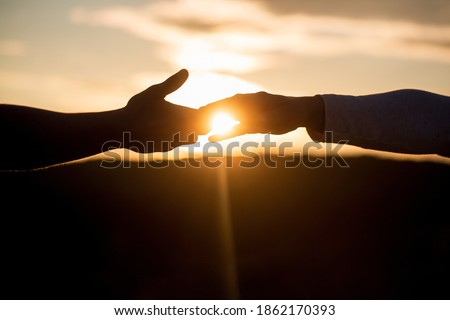 Outstretched hands, salvation, help silhouette, concept help. Giving a helping hand. Rescue, helping gesture or hands. Two hands silhouette on sky background, connection or help concept. #1862170393