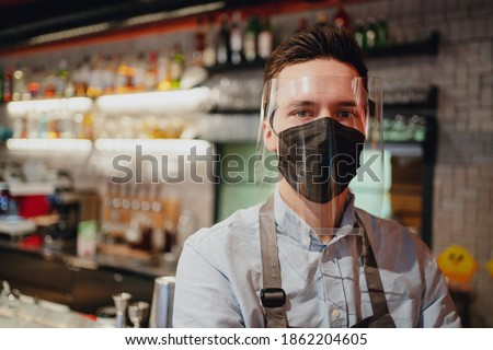 a restaurant employee wearing a protective mask against the covid pandemic virus cafe bistro waiter a young man of dark Caucasian appearance stands near the bar. workman's clothing in apron and shirt. Royalty-Free Stock Photo #1862204605