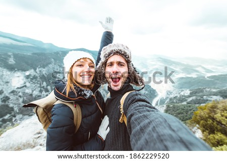 Happy couple taking a selfie hiking mountains - Successful hikers on the top of the peak smiling at camera  Royalty-Free Stock Photo #1862229520