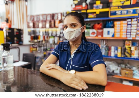 Young woman wearing face mask working in hardware store Royalty-Free Stock Photo #1862238019