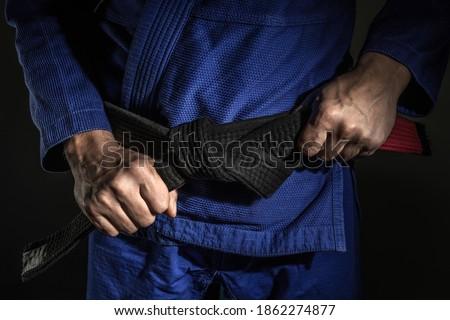 Close up on hand of unknown caucasian man holding brazilian jiu jitsu bjj black belt around his waist while wearing kimono gi in dark - martial arts mastery skill and confidence achievement concept Royalty-Free Stock Photo #1862274877