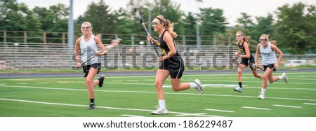 Opposing teams doing battle during a girls Lacrosse game, outdoors on playing field.