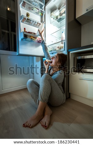 Woman in pajamas eating on floor and reaching milk from fridge #186230441