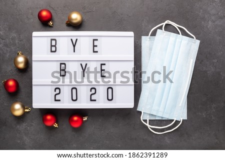 Lightbox with text BYE BYE 2020 with medical mask on dark background. Top view. New year celebration. Happy New Year 2021 concepts - Image