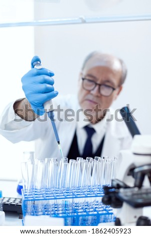 Senior pharmaceutical scientist in modern laboratory using dropper dispenser with genetic material. Professional chemist using pippete with blue solution for microbiology tests. Royalty-Free Stock Photo #1862405923