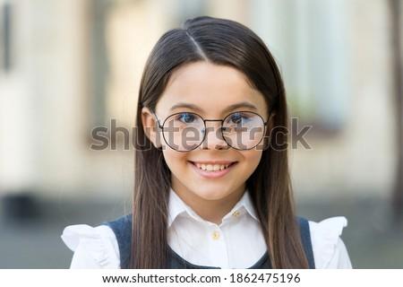 Smart at first sight. Happy kid wear eyeglasses outdoors. Sight test. Eye examination. Pediatric ophthalmology. Fashion eyewear. Trendy glasses. Vision correction. Optician salon. School education. Royalty-Free Stock Photo #1862475196
