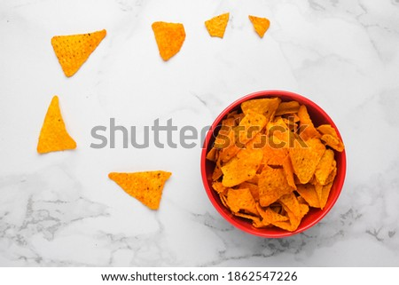 A picture of hot and spicy nachos with on the marble table insight.
