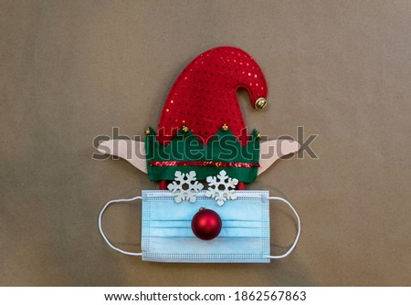 Festive elf hat with face mask and ornaments for winter, Christmas, New Year's, December, brown paper background flat lay