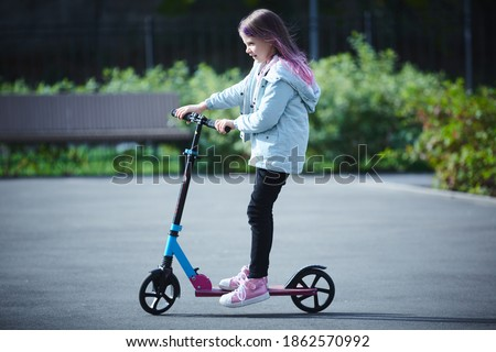 Happy beautiful girl is riding along the street on the kick scooter on a windy day. Baby having free time playing. The concept of a healthy lifestyle. Kids sport Royalty-Free Stock Photo #1862570992