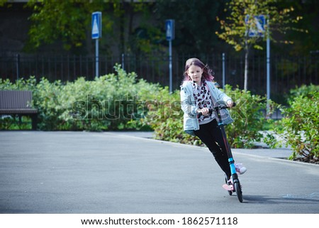 Happy beautiful girl is riding along the street on the kick scooter on a windy day. Baby having free time playing. The concept of a healthy lifestyle. Kids sport Royalty-Free Stock Photo #1862571118